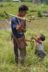 A farmer interacting with his daughter while she is holding a plant. Photo taken in Mawhiang, West Khasi Hills.